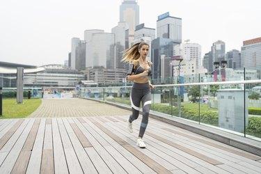 Blond sportswoman running on bridge
