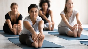 Indian woman practicing yoga at group lesson, Seated forward bend