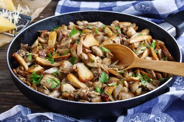 fried porcini mushrooms with parsley in skillet