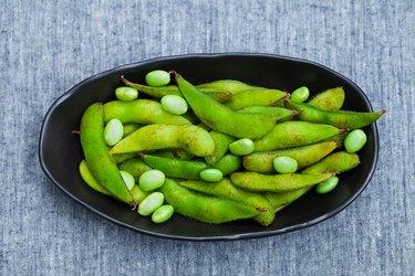 Fresh edamame green beans in black bowl. Grey textile background. Top view.