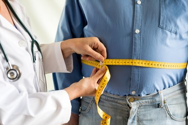 close up of doctor in white coat measuring man's hard visceral belly fat with yellow tape measure