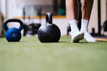 Man weight lifting in socks to improve exercise.