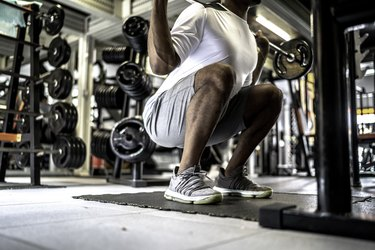 close up of man doing squat with barbell in gym