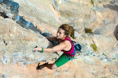 Top View of Girl Rock Climber hanging high rocky Wall