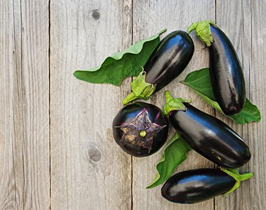 Ripe eggplants on a wooden background. Top view, flat lay.