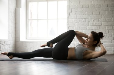 Young attractive woman doing bicycle crunches pose, white loft s
