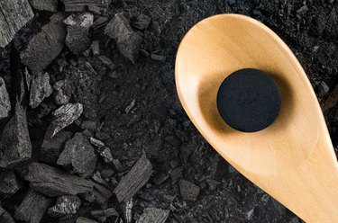activated carbon pill medicine in wooden spoon on ground charcoal texture background, top view