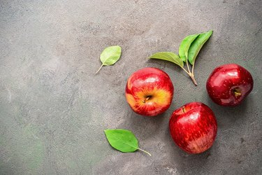 Three ripe bright red apples with green leaves on a rustic textured background, top view. Copy space