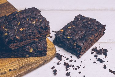 Vegan zucchini flourless paleo brownies and pumpkin brownies (keto, low carb and gluten-free) on a wooden background.