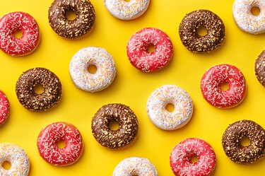 Pink, white and brown donuts in a pattern on a yellow background