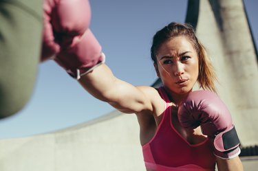 Sportswoman practicing boxing outdoors