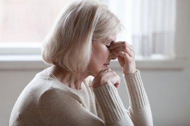 Fatigued upset older woman massaging nose bridge feeling eye strain