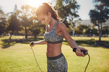 Fit young woman with jump rope in a park
