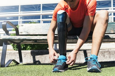 Disabled man athlete ready for training with leg prosthesis.