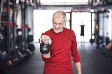 Senior man exercising with kettlebell in gym