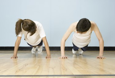 Teenage boy and girl (12-14) doing push-ups side by side in gymnasium