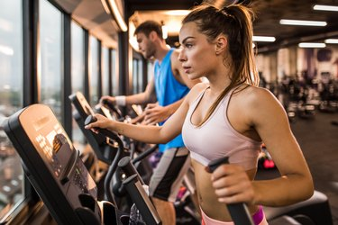 Determined woman exercising on a cross trainer in a gym