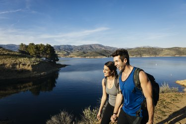 Mid adult couple walking on footpath by lake