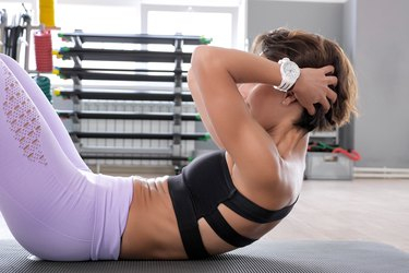 Mature woman is doing abs crunch exercise slowly on mat in gym.