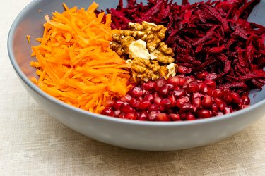 Salad of grated red beets carrots pomegranates and walnuts