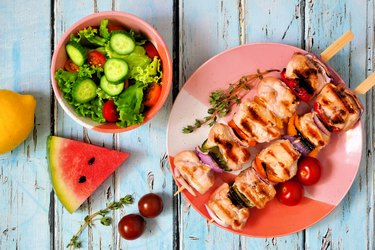 Grilled chicken and vegetable skewers with salad and watermelon, above scene over blue wood