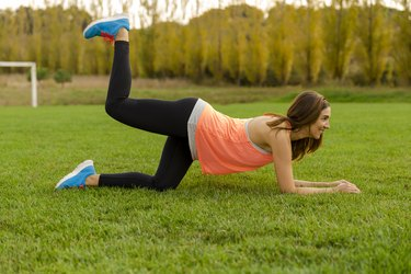 woman wearing orange tank top doing donkey kick variations in a park on grass