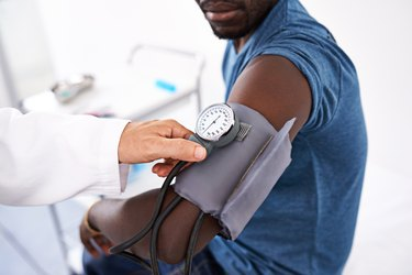 Close view of a doctor taking a man's blood pressure