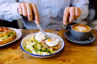 Man eating breakfast with poached eggs, fresh salad and coffee