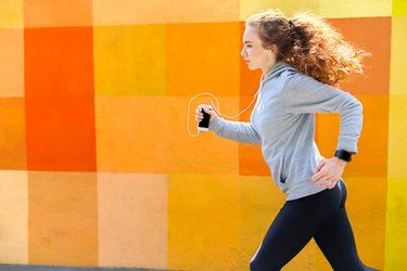 Side view of woman running against bright wall