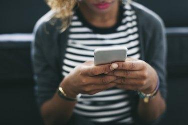 Woman wearing striped shirt holding smartphone