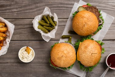 different hamburger on wooden table with sauces, fries and pickl