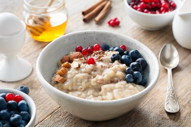 Healthy breakfast food oatmeal porridge, boiled egg, honey and berries.