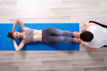 Young Woman Doing Sit Ups With Help Of Trainer