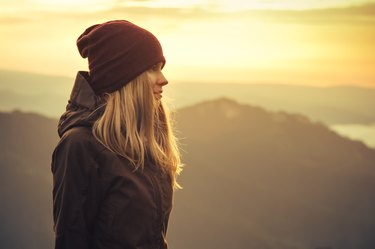 Young Woman standing alone outdoor with sunset mountains