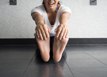 Smiling woman grabbing her feet to stretch hamstrings