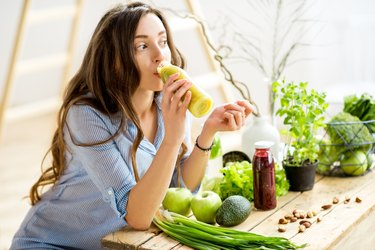 A woman drinking a green juice, surrounded by green food
