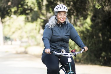 Older woman wearing a helmet and biking outdoors