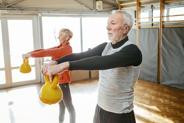 Senior couple in gym working out using kettle bells