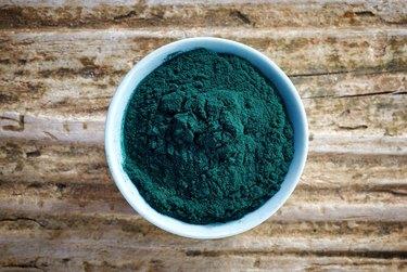 White bowl of dark green spirulina algae powder