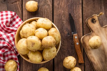 washed potato in a bowl on wooden table