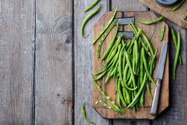 Green beans on wooden cutting board. Top view