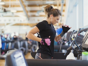 Woman running on treadmill at gym with headphones