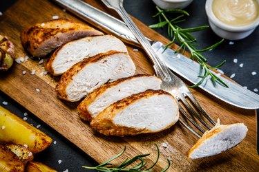 Grilled leftover turkey breast slices on wooden plank