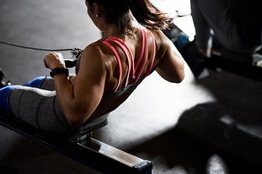 Woman working out on rowing machine, San Diego, California, USA
