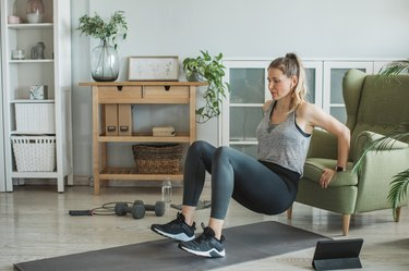 Woman doing triceps dips from a chair in her living room during an at-home workout
