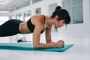 Muscular young woman doing planks exercise