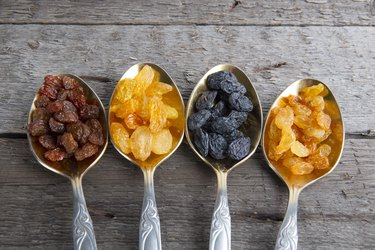 Different colored raisins in metal spoons on wooden table