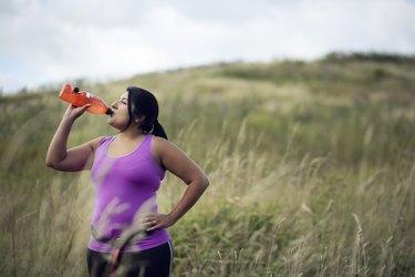 Female jogger drinking diet supplements like Plexus from bottle