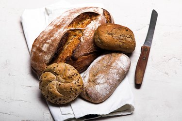 Tasty dark bread and buns  on white background, copy space. Bakery products, wholemeal bread and brown whole wheat buns