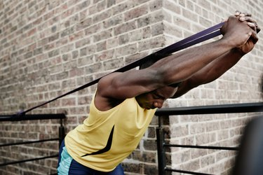Man doing an overhead triceps extension with resistance band against a brick wall